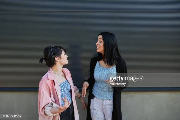 cheerful teenage sisters talking and smiling outdoors - 18 19 years stock pictures, royalty-free photos & images