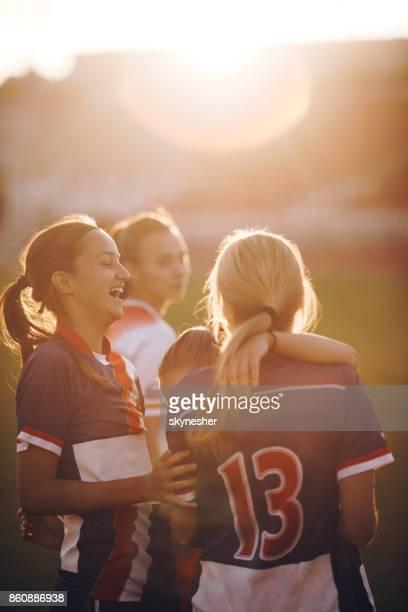 joyeux teenage footeux rire sur un terrain de jeu au coucher du soleil. - sport d'équipe photos et images de collection