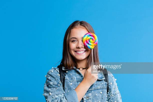 cheerful teenege girl holding lollipop - white jacket stock pictures, royalty-free photos & images