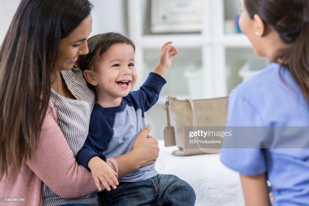 Cheerful toddler boy smiles at pediatrician : Stock Photo