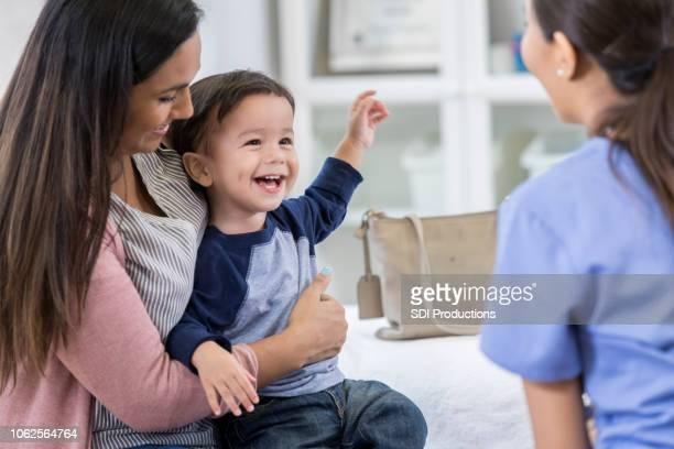 cheerful toddler boy smiles at pediatrician - emergency medicine stock pictures, royalty-free photos & images