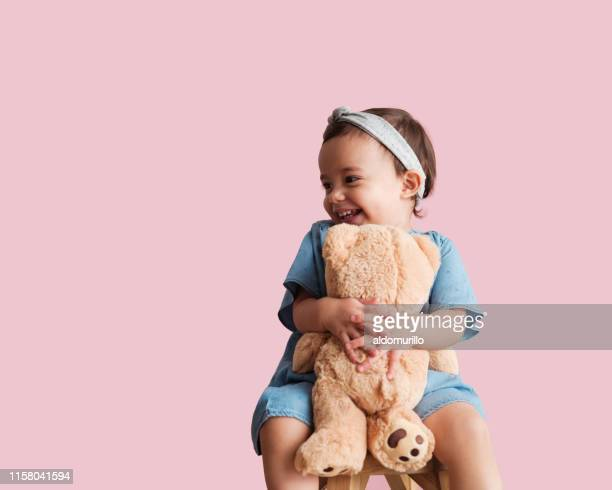 cheerful toddler with her favorite toy - stuffed toy stock pictures, royalty-free photos & images