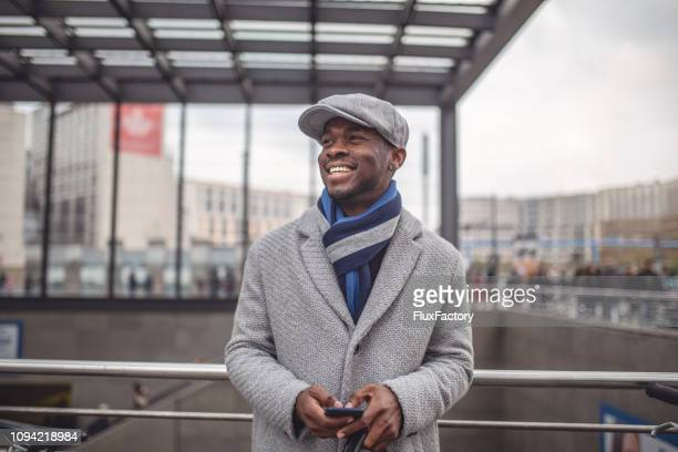 cheerful tourist businessman standing next to a subway entrance - winter coat stock pictures, royalty-free photos & images