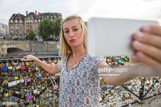 Cheerful tourist in Paris, France taking selfie using mobile phone