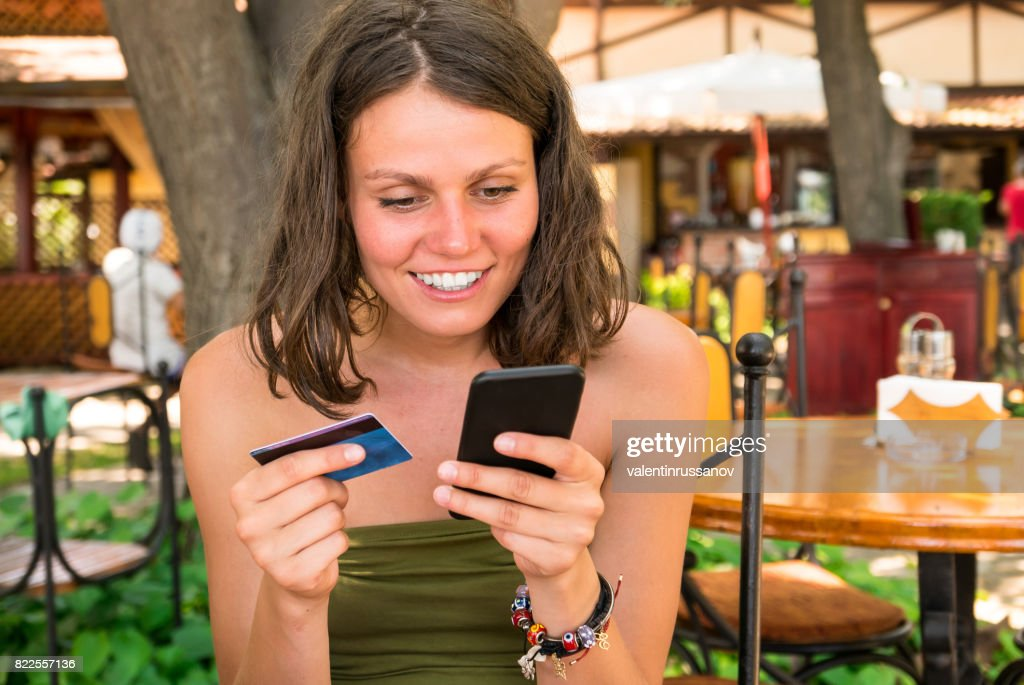 Cheerful tourist using smart phone and credit card : Stock Photo
