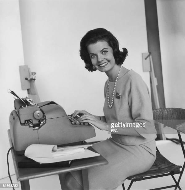 A cheerful typist at her work circa 1965