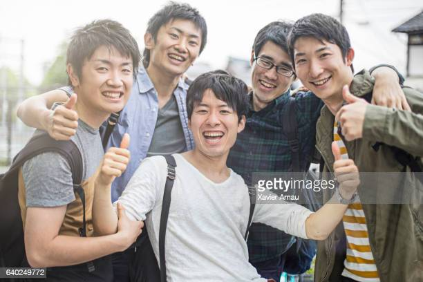 Cheerful university students gesturing thumbs up