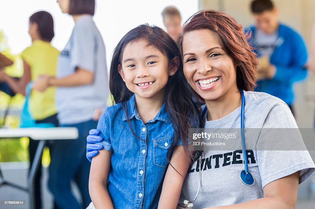 Cheerful volunteer and young girl smiling and embracing : Stock Photo