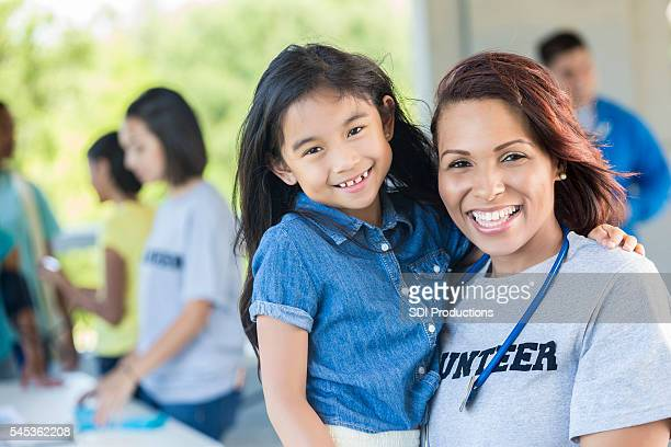 Cheerful volunteer holding an adorable young girl