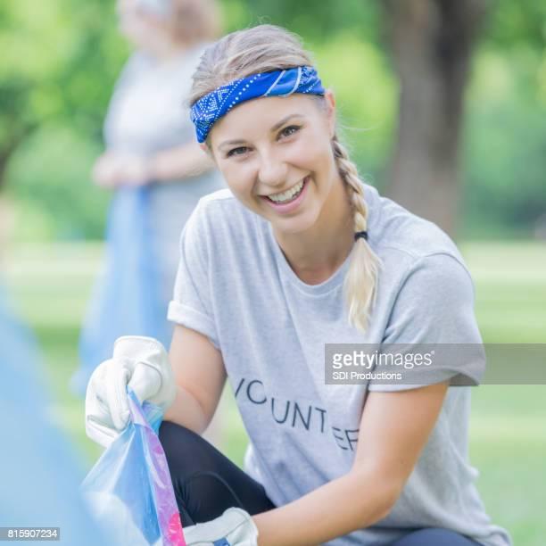 Cheerful volunteer picks up trash in her community