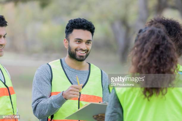 cheerful volunteers discuss cleanup project - reflective clothing stock pictures, royalty-free photos & images