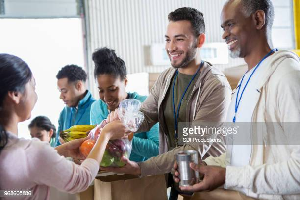 cheerful volunteers receive donations during food drive - volunteer stock pictures, royalty-free photos & images