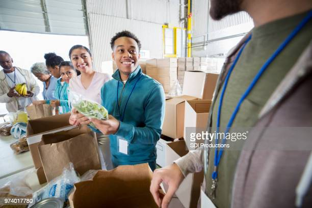 cheerful volunteers working in food bank - non profit organization stock pictures, royalty-free photos & images