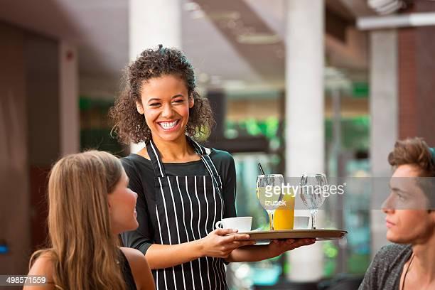 Cheerful waiter serving drinks