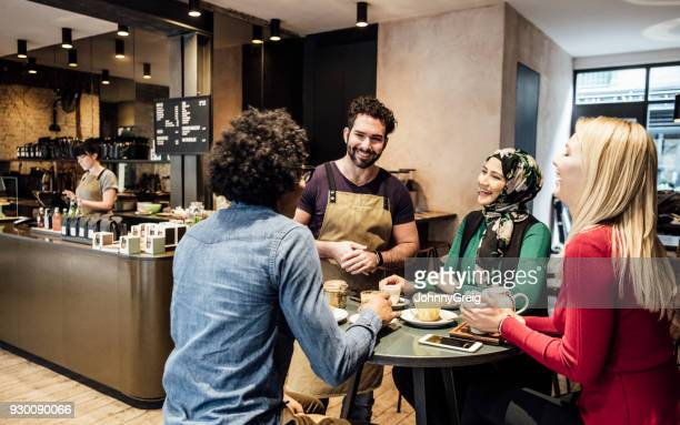 Cheerful waiter talking to thee customers in cafe and smiling