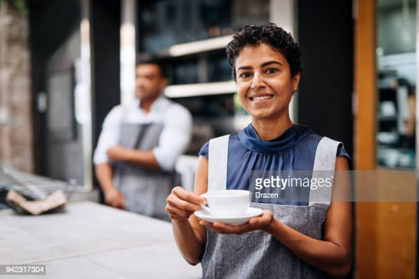 Cheerful waitress holding cup of roasted arabic coffee blend