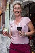 cheerful waitress with wine glasses doorway