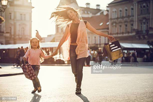 Cheerful woman and little girl running with shopping bags.