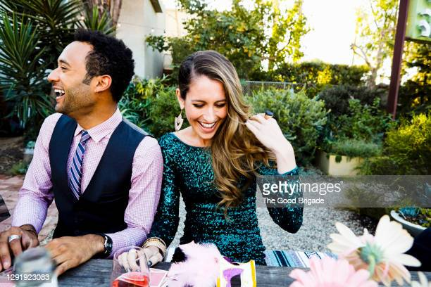 cheerful woman and man enjoying while sitting at dining table in back yard during party - cocktail dress stock pictures, royalty-free photos & images