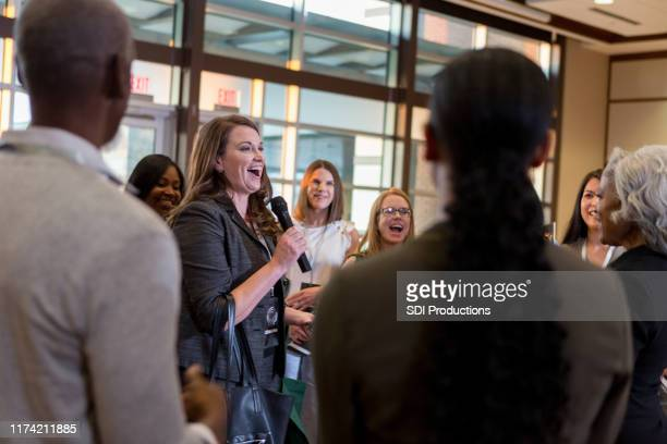 cheerful woman ask question during town hall meeting - town hall stock pictures, royalty-free photos & images