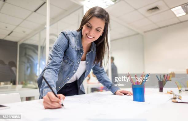 cheerful woman at a co working space focused on her designs smiling - interior design foto e immagini stock