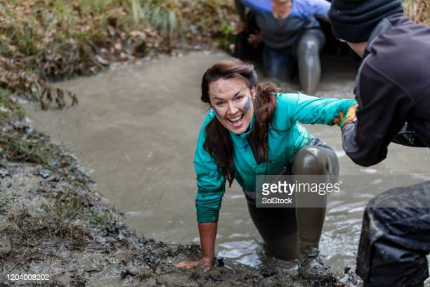 cheerful woman being helped out of muddy pool - caucasian appearance stock pictures, royalty-free photos & images
