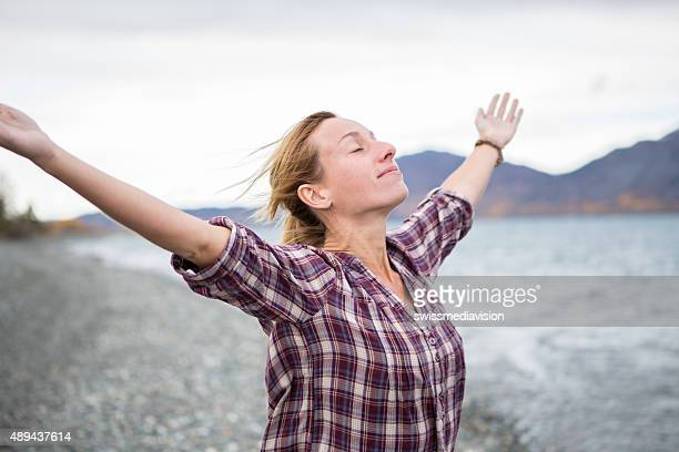 Cheerful woman by the lake arms outstretched for positive emotion