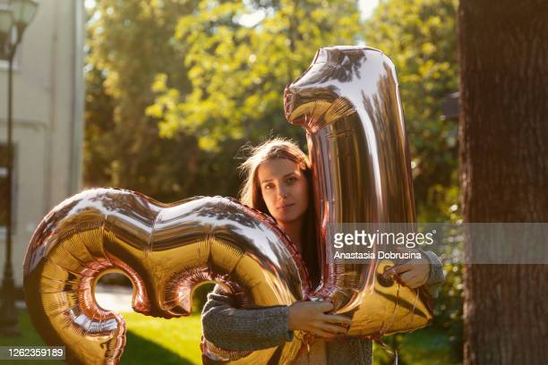 cheerful woman celebrates a thirty one years birthday with big golden balloons - 30 34 years imagens e fotografias de stock