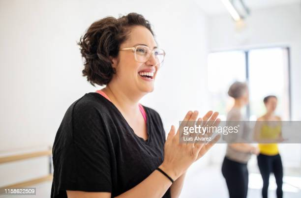 cheerful woman clapping hands at fitness studio - applaudieren stock-fotos und bilder