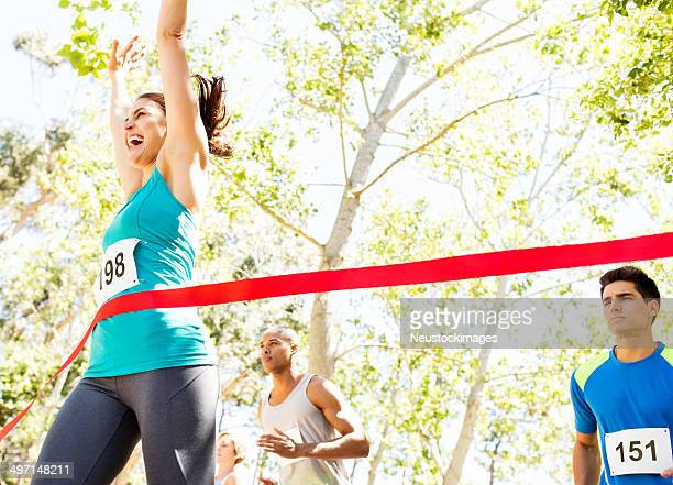 cheerful woman crossing finish line of marathon - finish line stock pictures, royalty-free photos & images
