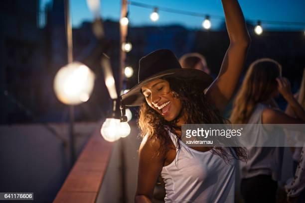 Cheerful woman dancing during terrace party