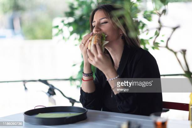 cheerful woman eating a sandwich - sausage sandwich stock pictures, royalty-free photos & images