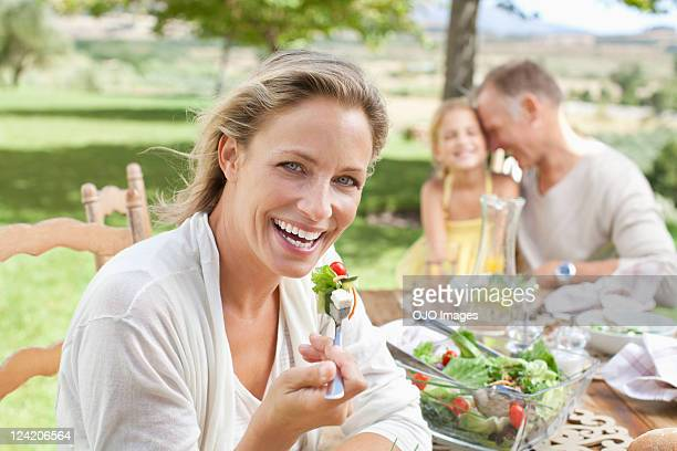 Cheerful woman eating salad with man and daughter in the background at lawn