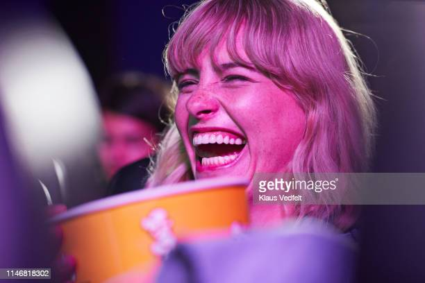 cheerful woman enjoying at movie theater - industria cinematografica foto e immagini stock