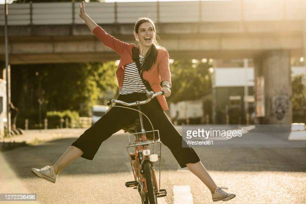 cheerful woman enjoying cycling on street in city during sunny day - hand raised stock pictures, royalty-free photos & images
