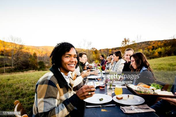 cheerful woman enjoying dinner party in field with friends - warm clothing stock pictures, royalty-free photos & images