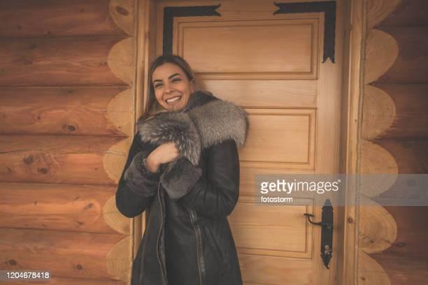 寒い冬の日に彼女のフェイクファーコートを楽しむ陽気な女性 - 毛皮のコート ストックフォトと画像