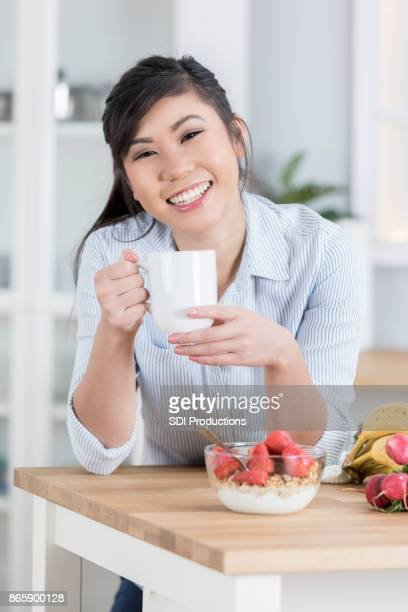 cheerful woman enjoys healthy food break - lap body area stock photos and pictures