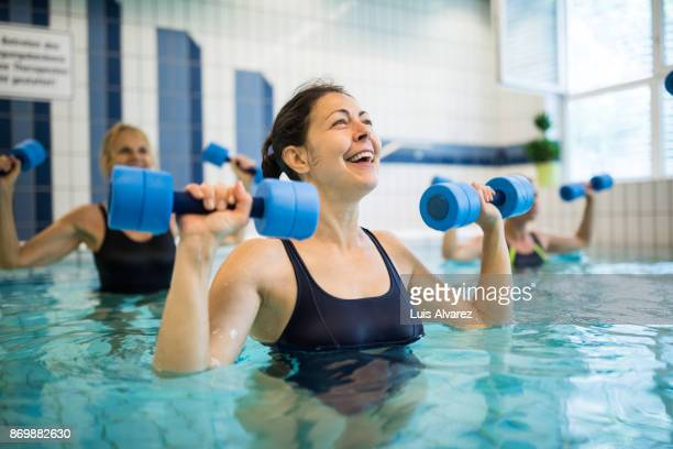 Cheerful woman exercising with dumbbells against friends in swimming pool