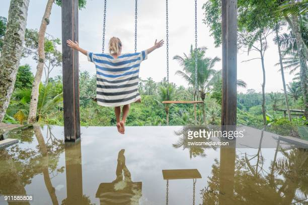 Cheerful woman experiencing swing in the jungle, Asia