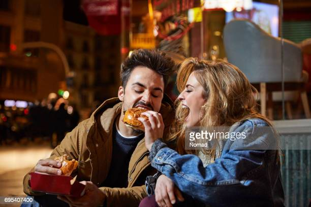Cheerful woman feeding burger to man at night
