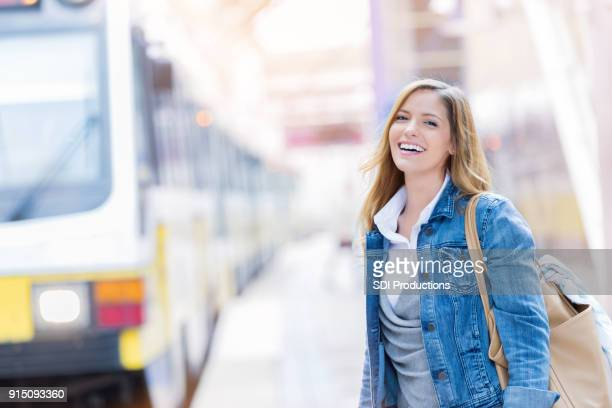 cheerful woman gets ready to board commuter train - mid adult stock pictures, royalty-free photos & images
