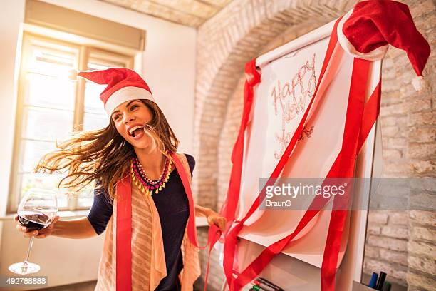 Cheerful woman having fun at New Year's office party.