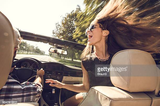 Cheerful woman having fun in cabriolet with her boyfriend.