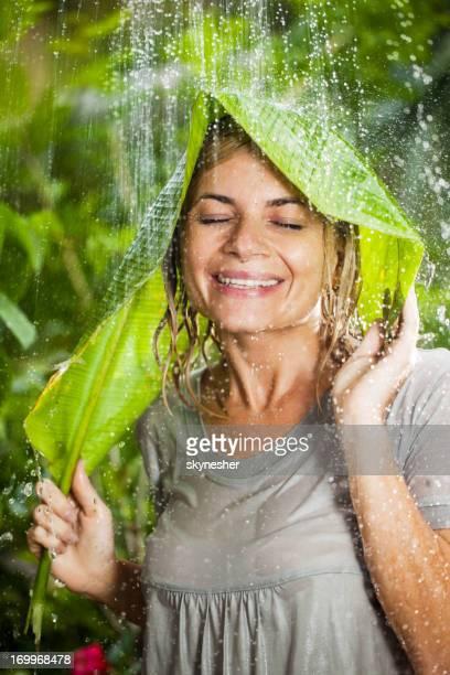 Cheerful woman having fun in jungle during tropical rain.
