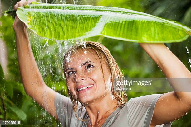 Cheerful woman having fun in the jungle during tropical rain.