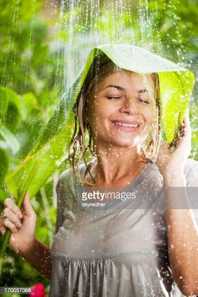 Cheerful woman having fun in the jungle during tropical rain.