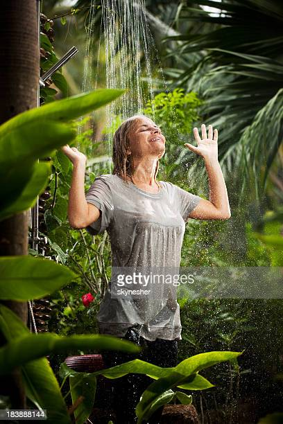 cheerful woman having fun in the jungle during tropical rain. - wet shirt stock photos and pictures