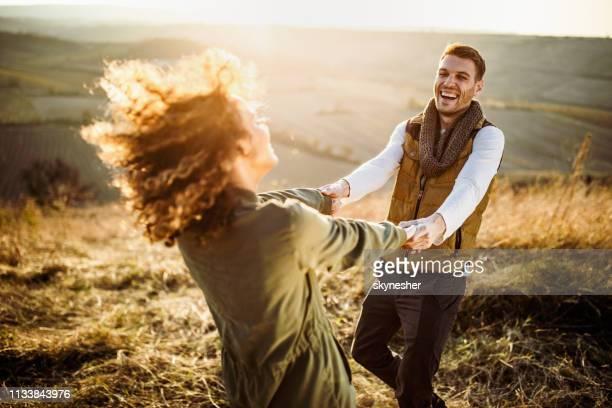fröhliche frau, die spaß beim spinnen mit ihrem freund auf einer wiese hat. - sorglos stock-fotos und bilder