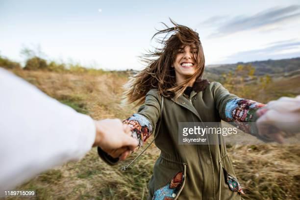 femme gaie ayant l'amusement tout en tournant avec son petit ami dans la nature. - enthousiaste photos et images de collection